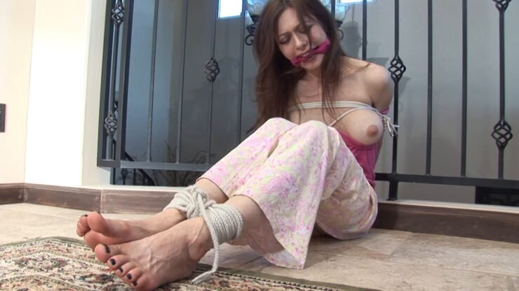 Natasha tied up seated on the floor with cleave gagged face