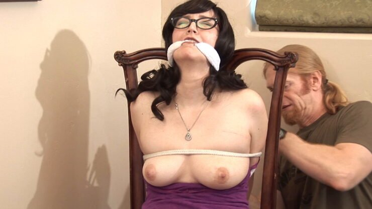 Quimm's hands are bound behind the chair back and she squirms in her bondage