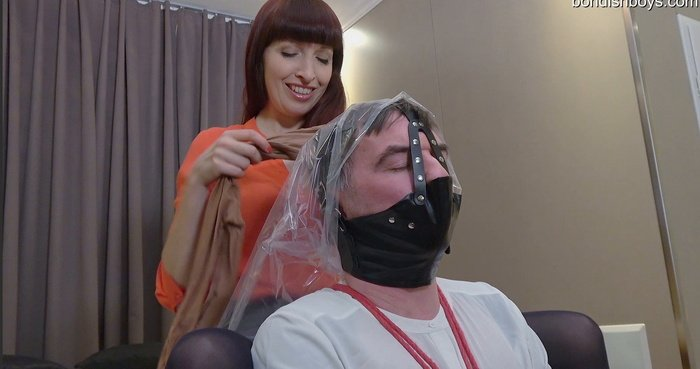 Bound slave in a tight gag and a bag on his head