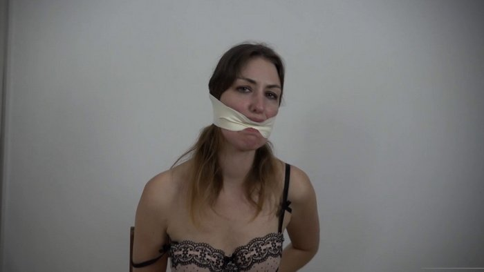 Lola on a chair with her hands tied behind her back gets gagged with microfoam tape
