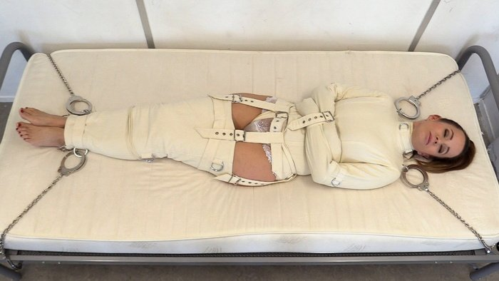 Cindy is chained to the bed in a straitjacket and straitjackets
