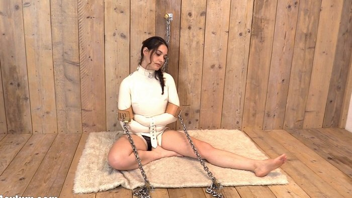 Maddie chained to the floor and to the wall in the straitjacket