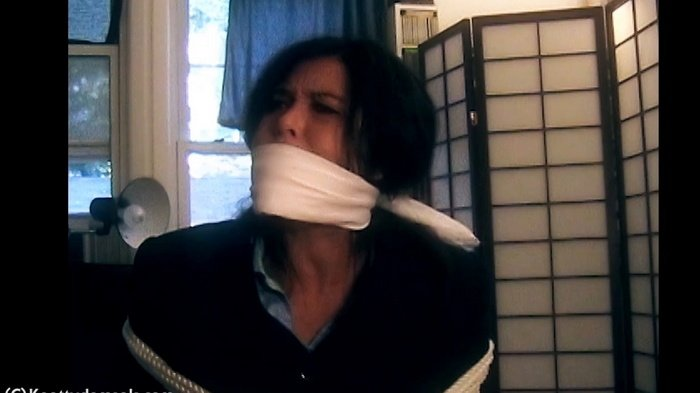 Tomiko alone to a chair, bound and gagged