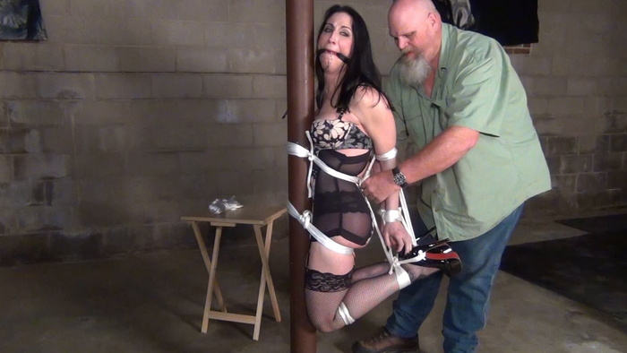 Raven tight gagged and hogtied to a pole
