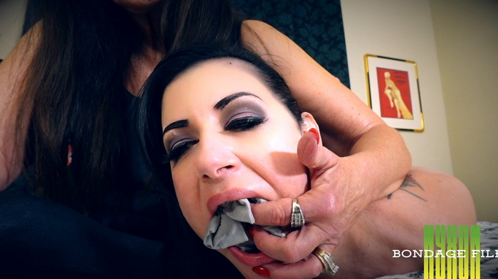 Burglar (JJ Plush) ties the Nyxon to a chair and covers her mouth with a large washcloth