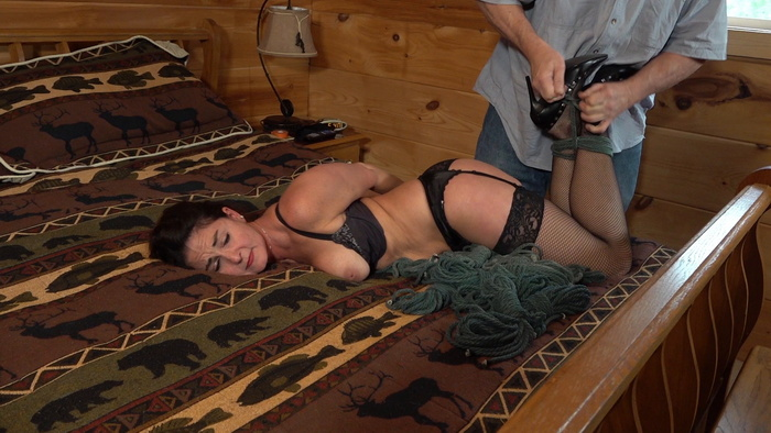 Carissa hogtied to the bed in the woods cabin